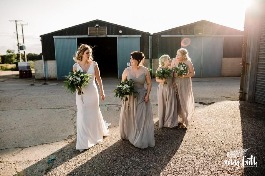 Bride and bridesmaids walking through farm in sunshine
