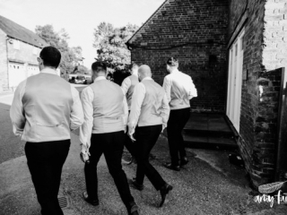 Groom and groomsmen walking away across farm in black and white