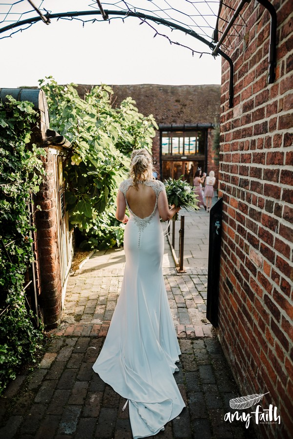 Back of bride as she walks through venue with her modern white backless dress and train