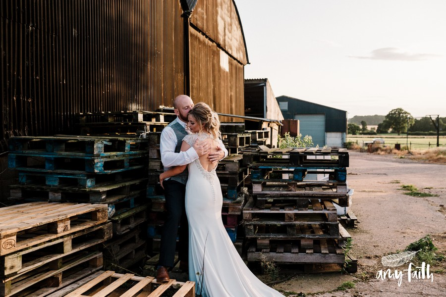 Bride and groom embracing in farm by pallets groom kissing brides head and his hands on her back