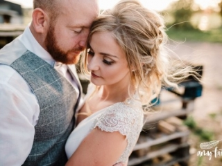 Bride and groom with heads together and eyes closed in sunset light with brides hair floating
