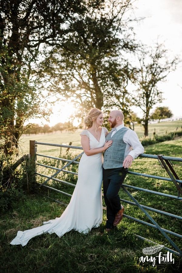 Smiling bride and groom leaning against farm gate with fields and trees in background in sunset light