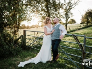 Bride and groom leaning on farm gate with fields and trees in background with sunset light
