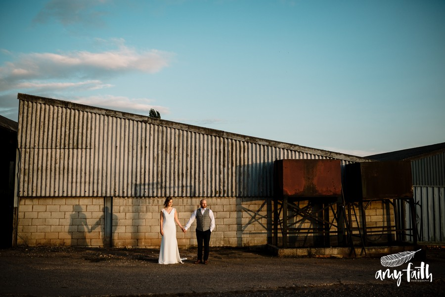 Bride and groom holding hands in centre of image in front of a diagonal barn with corrugated iron and blue skies in sunset light
