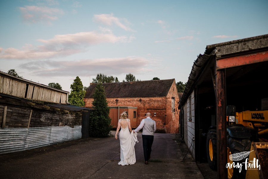 Groom holding brides dress as they walk away through farm yard at sunset with blue cloudy sky