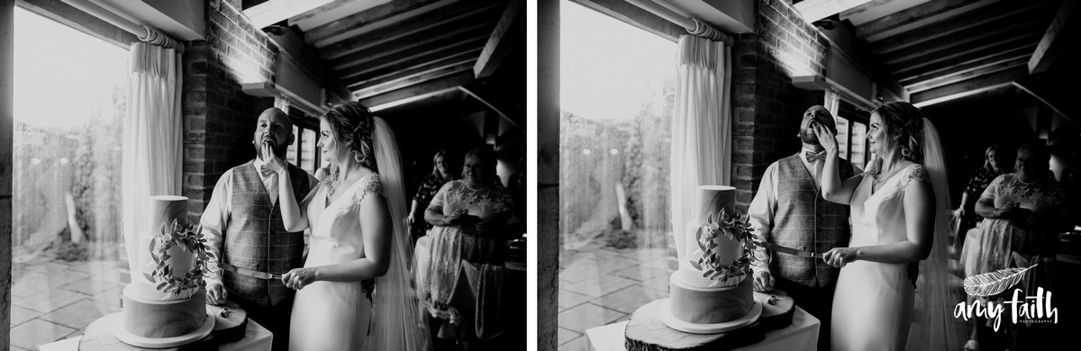Black and white documentary shot of bride shoving cake in grooms mouth