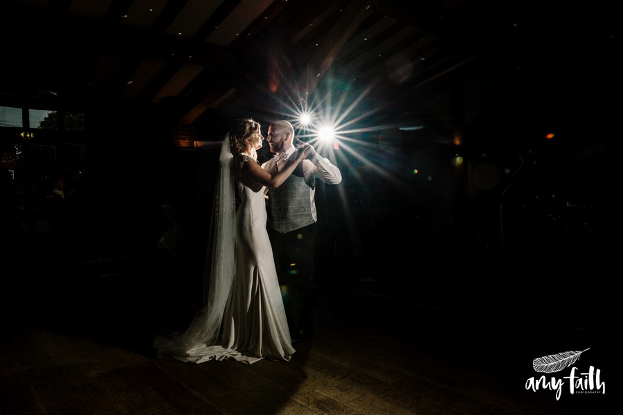 Bride and groom doing first dance under one bright light