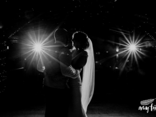 Black and white first dance bride and groom with fairy lights