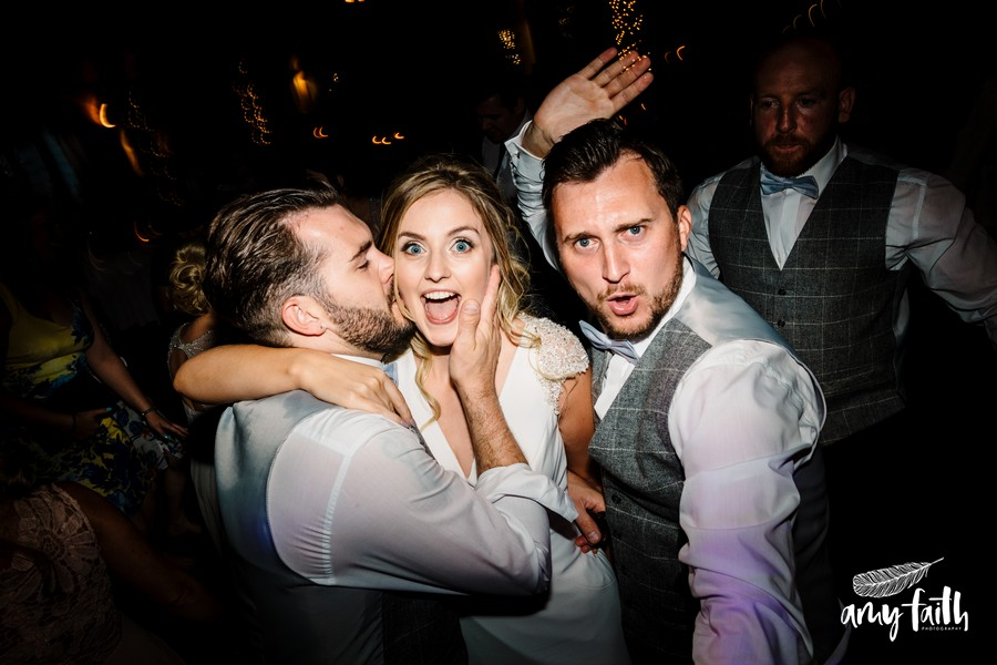 Groomsmen dancing with and kissing brides cheek
