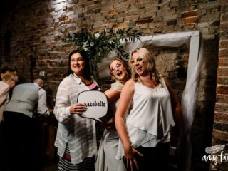 Bride posing for photobooth in funny glassese with two friends