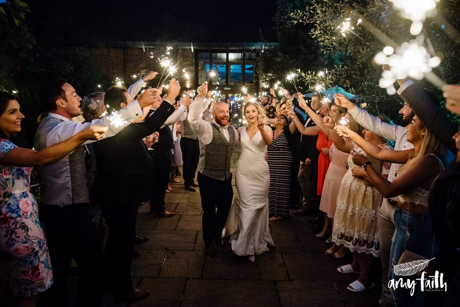 Laughing bride and groom dancing through all their guests with sparklers