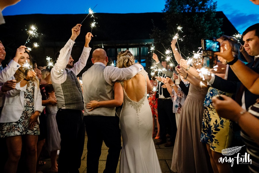Bride and groom walking away through crowd with sparklers at night