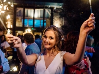 Smiling bride waving two sparklers at night