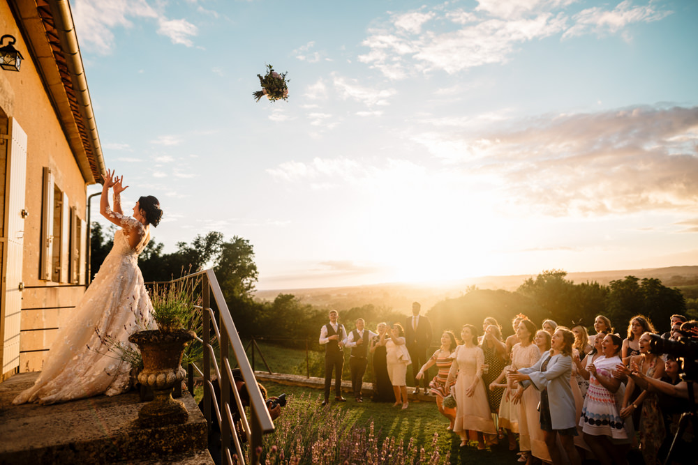 A bride throwing her bouquet through the sunset light to a crowd of women.
