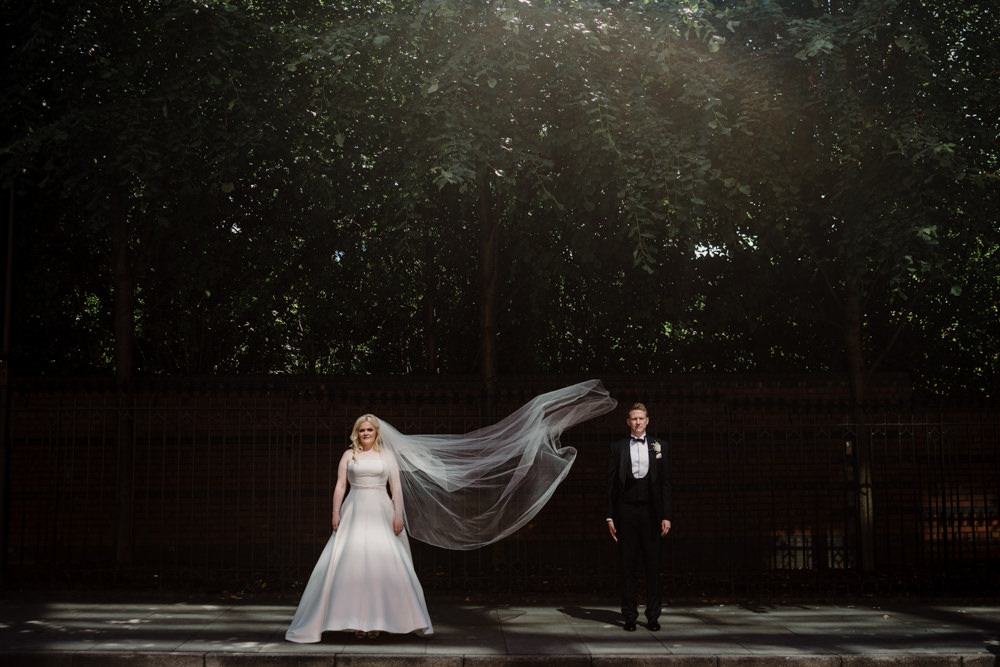 A bride and groom standing side by side with the brides veil floating in the air.