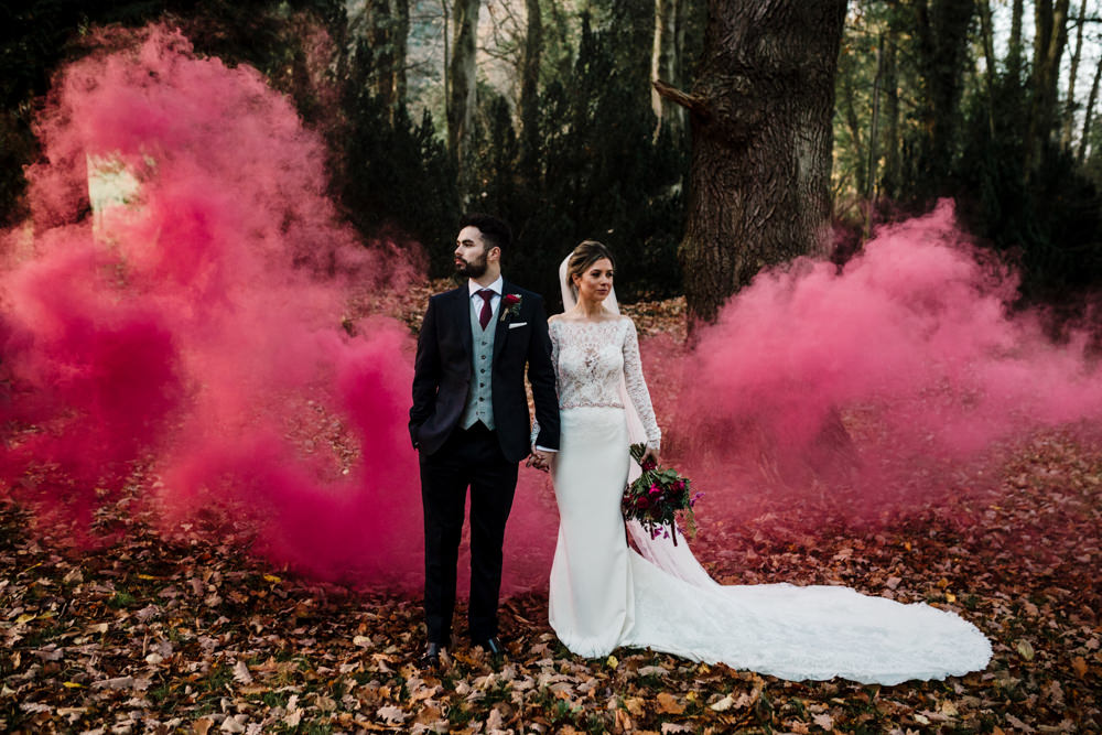 A bride and groom standing in front of a red smoke cloud.