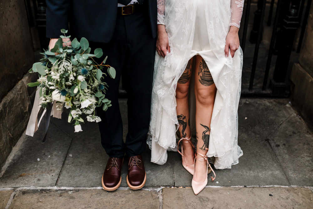 The legs of a bride & groom with tattoos on the brides legs and a bouquet held by the groom.