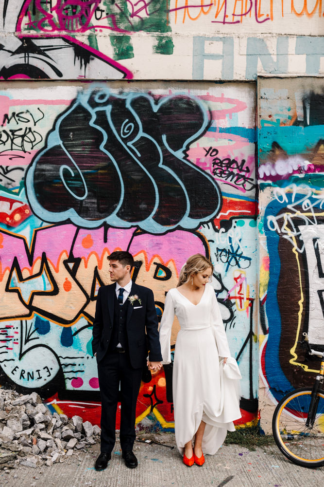A bride and groom standing in front of a graffiti wall.