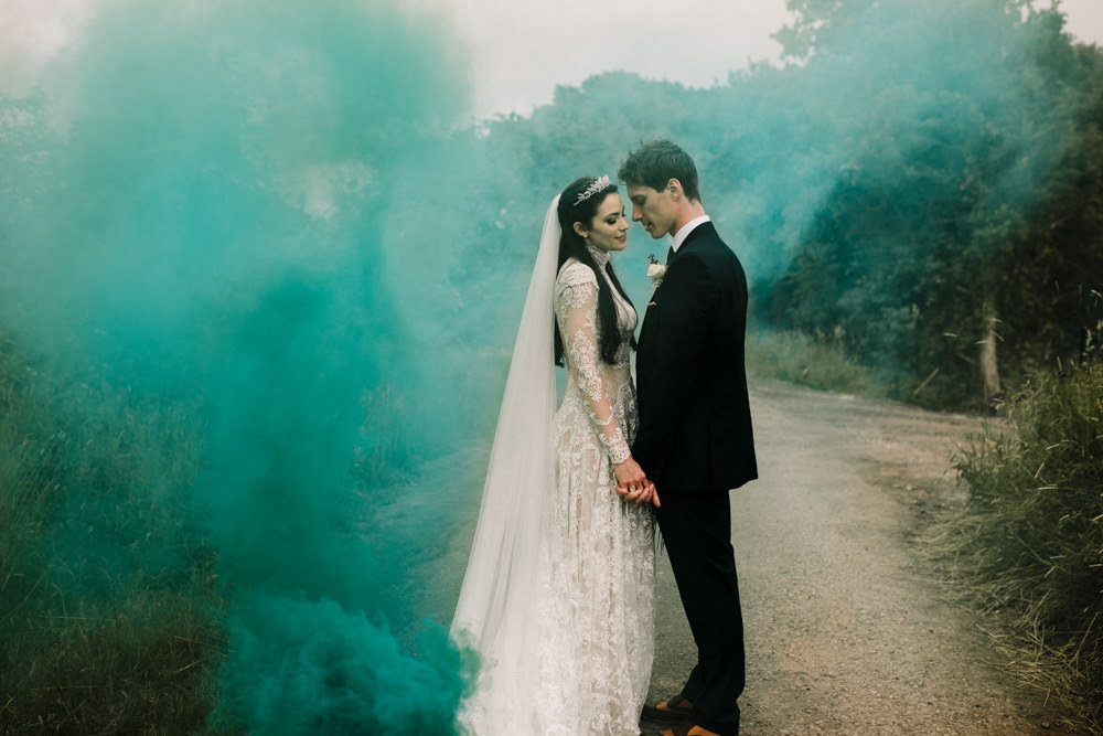 A bride and groom holding hands in front of a turquoise smoke cloud.