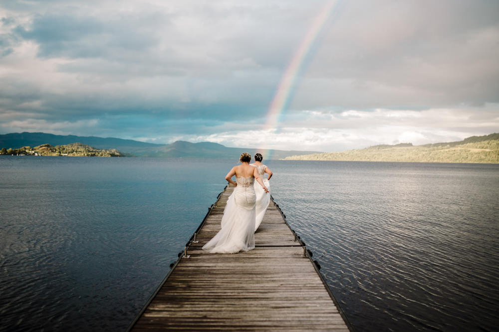 Two brides running down a jetty over a lake towards a rainbow.
