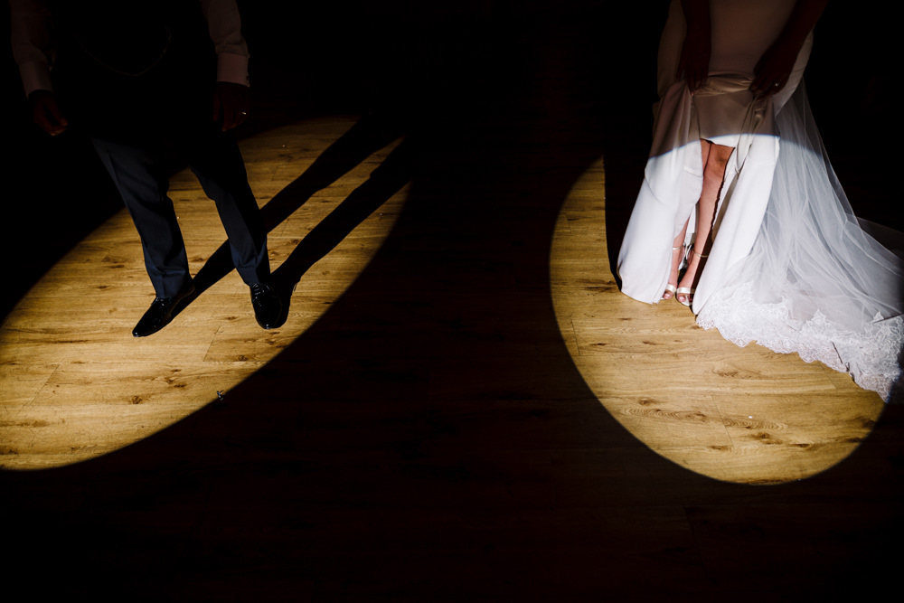 A bride and grooms legs standing in two spotlights.