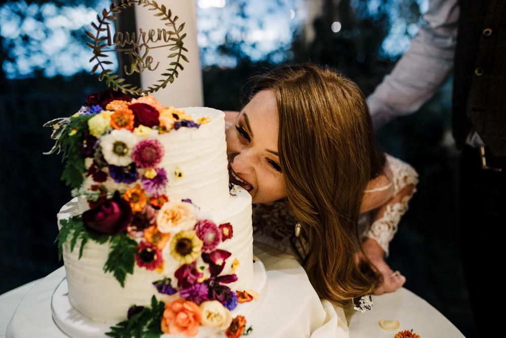 A bride biting her wedding cake.