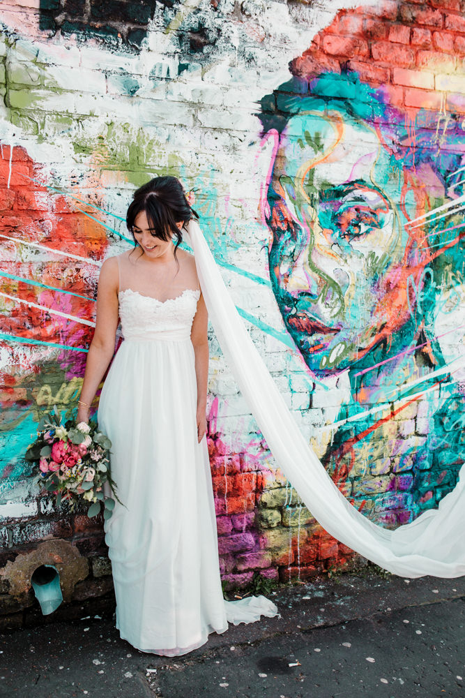 A bride standing in front of a graffiti wall.