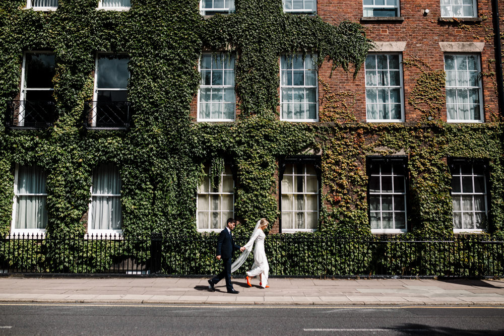 A bride and groom walking past a building covered in ivy.