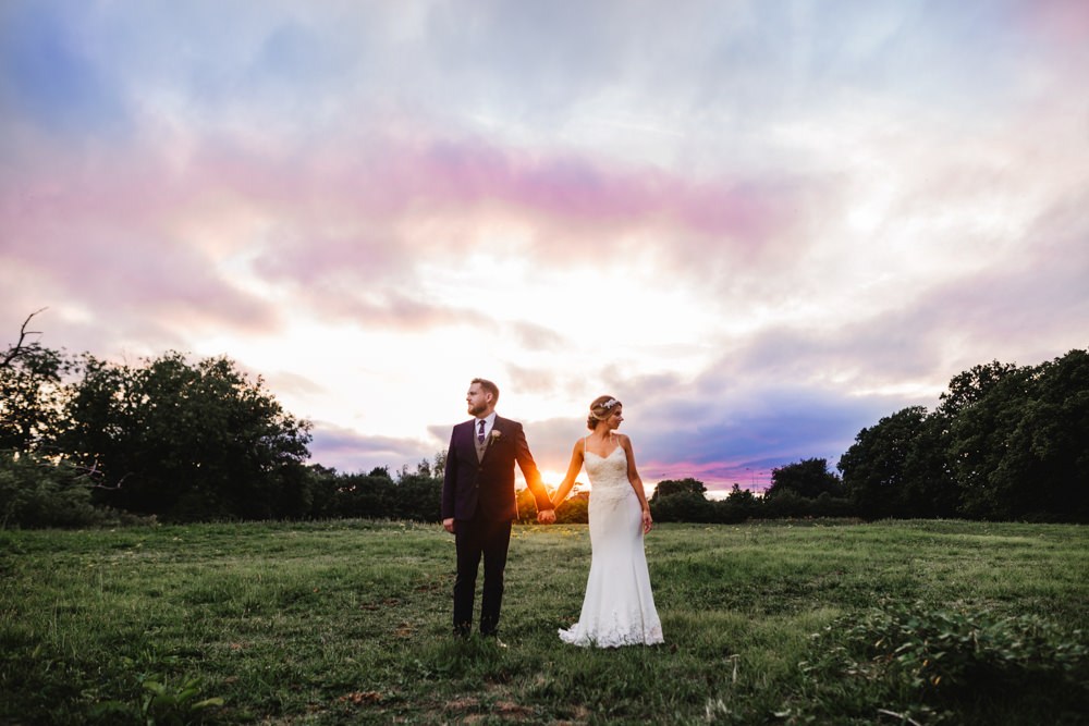 A bride and groom standing in front of a colourful sunset sky.