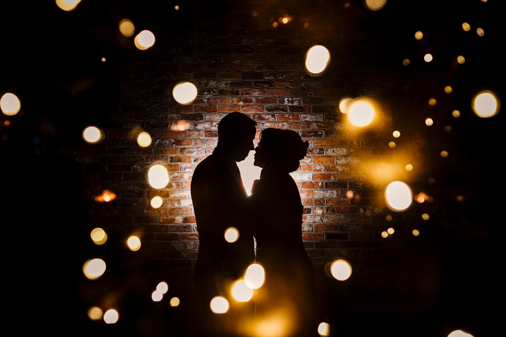 A silhouette of a man and woman in front of a brick wall with lights all around.