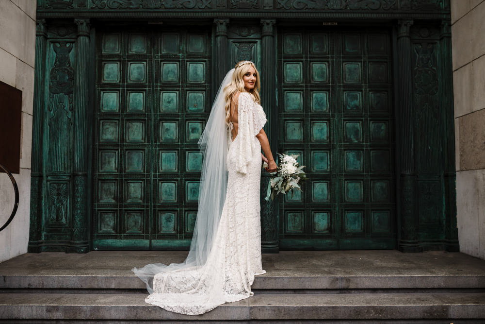 A bride in a lace dress standing in front of a turquoise door.