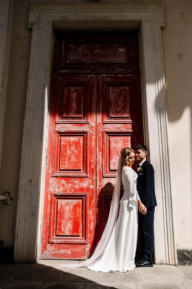 A bride and groom standing in front of an old red door.