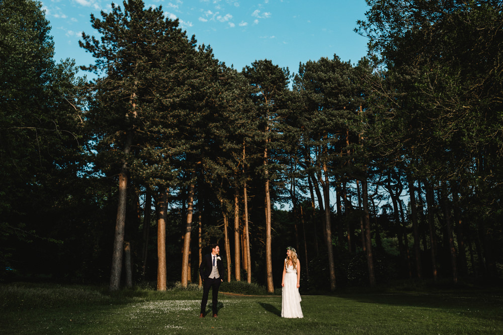 A bride and groom standing separately in a sunny field with tall trees.