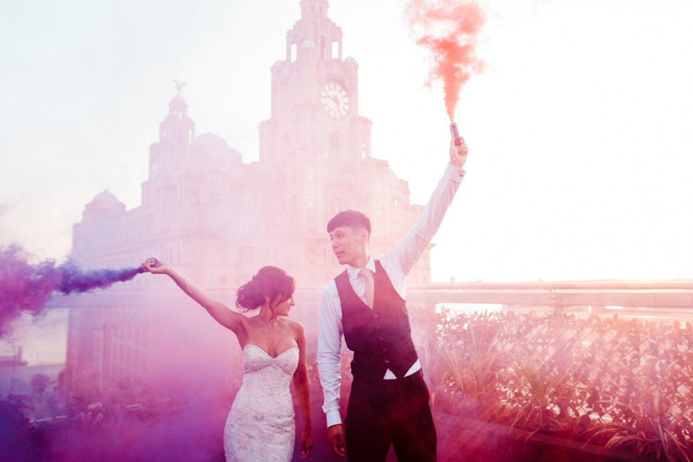 A bride and groom waving smoke bombs in front of a building.