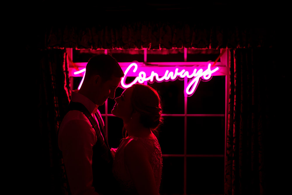 A bride and groom standing in front of a neon sign in a window.