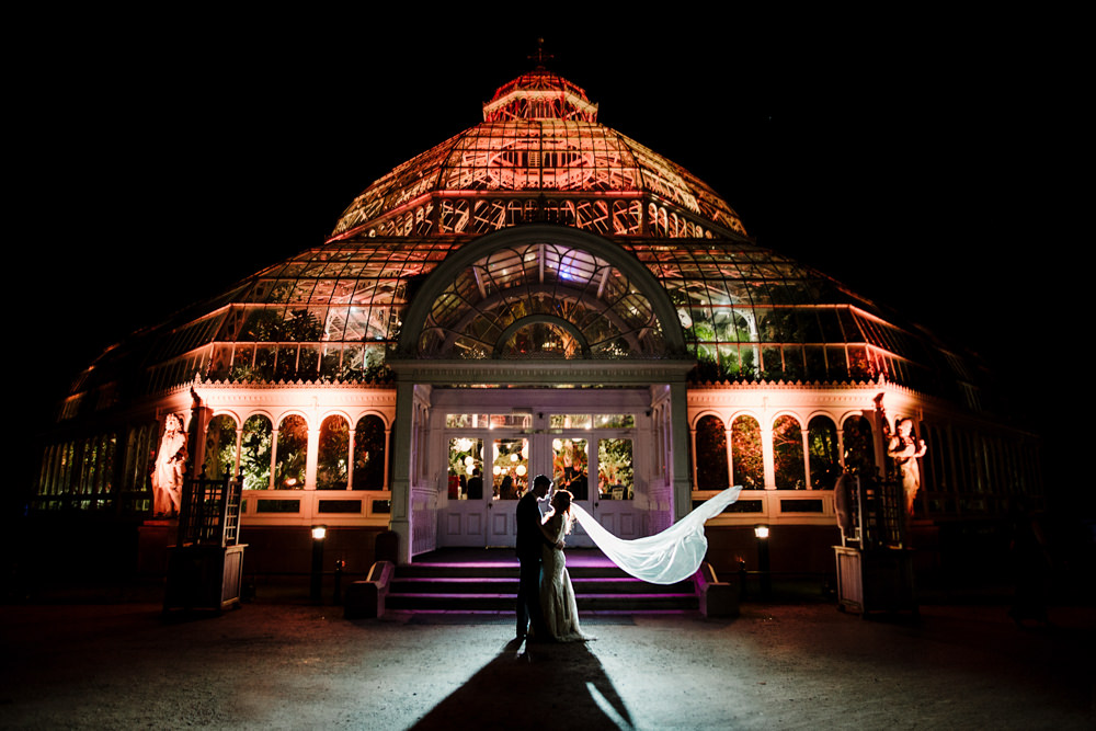 A bride and groom silhouetted in front of a large palm house.