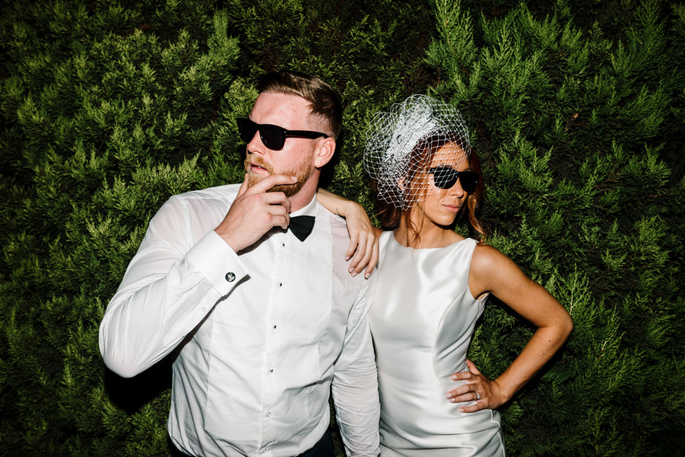 A bride and groom looking cool in sunglasses in front of a large bush.