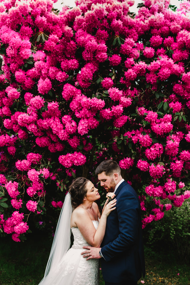 A bride and groom standing under a large bush of pink flowers.