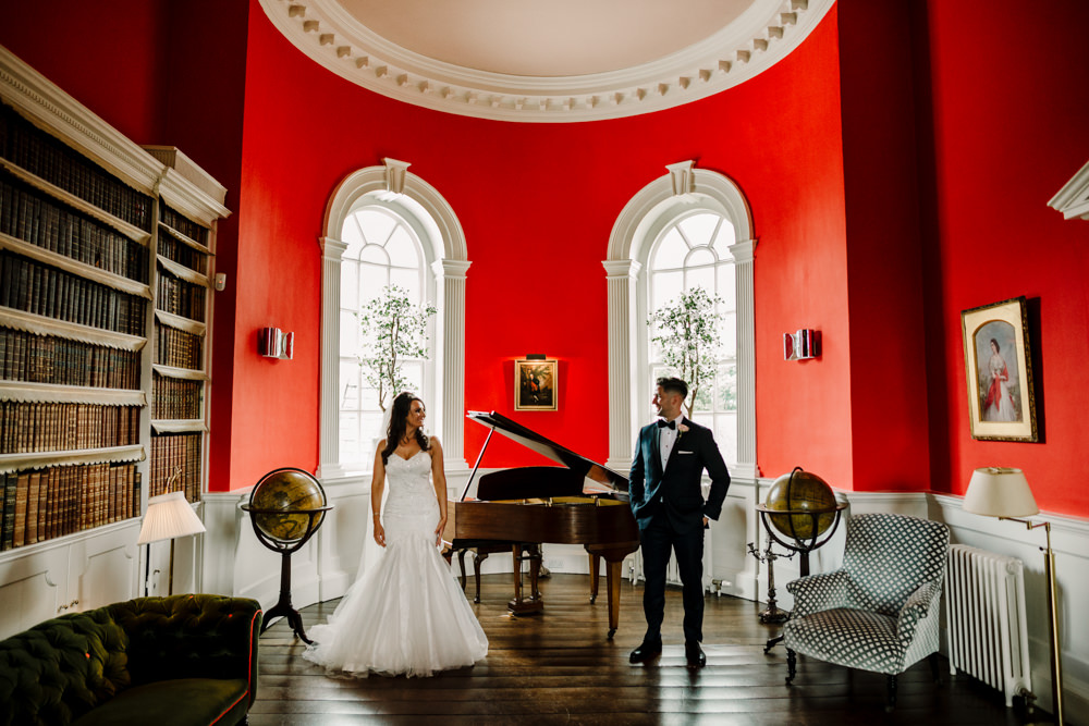 A bride and groom standing in a large red room with a piano.