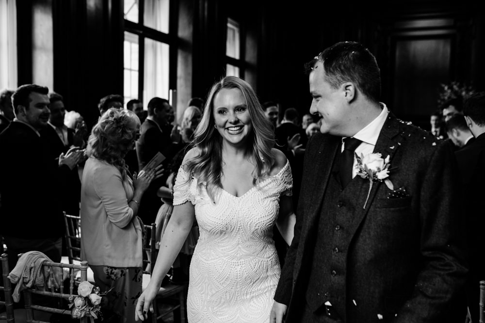 A black and white shot of a bride and groom walking down the aisle.