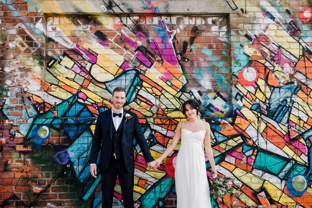 A bride and groom standing hand in hand in front of a graffiti wall.