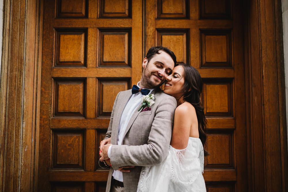 A bride hugging a groom from behind in front of a door.