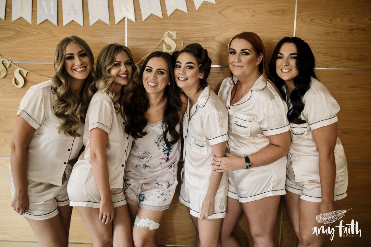 Six bridesmaids smiling together.