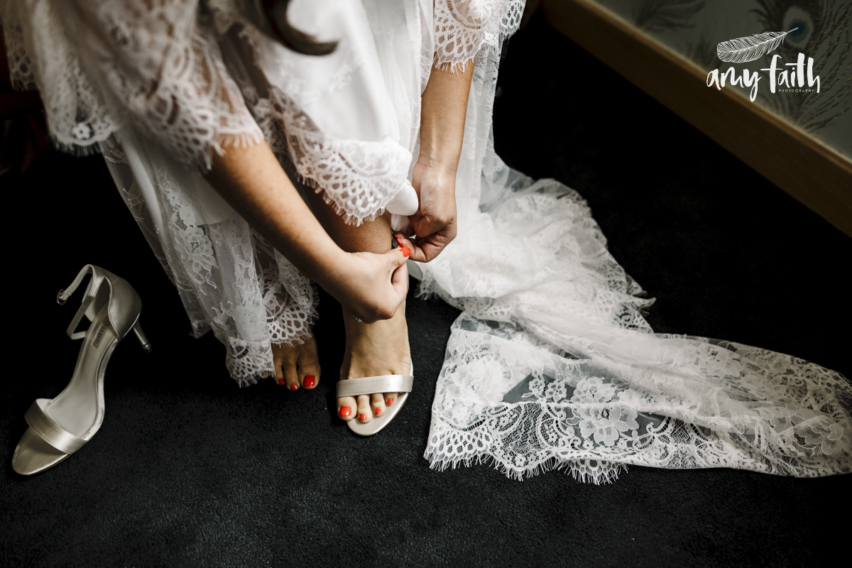 A bride fastening her shoe buckle.