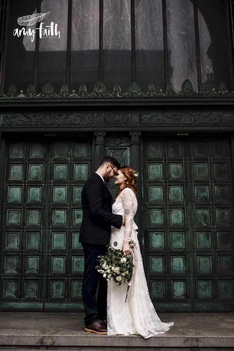 A bride and groom hugging in front of a green door