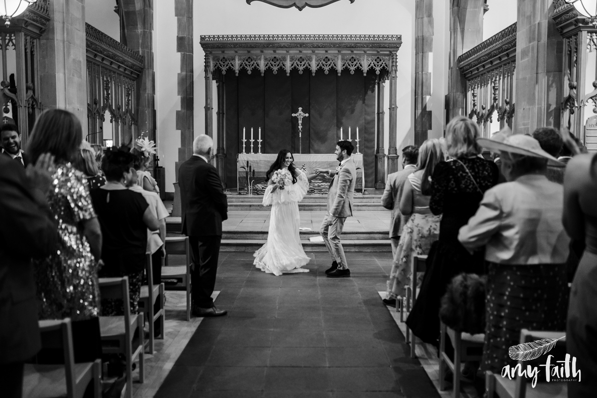 A bride and groom dancing down the aisle.