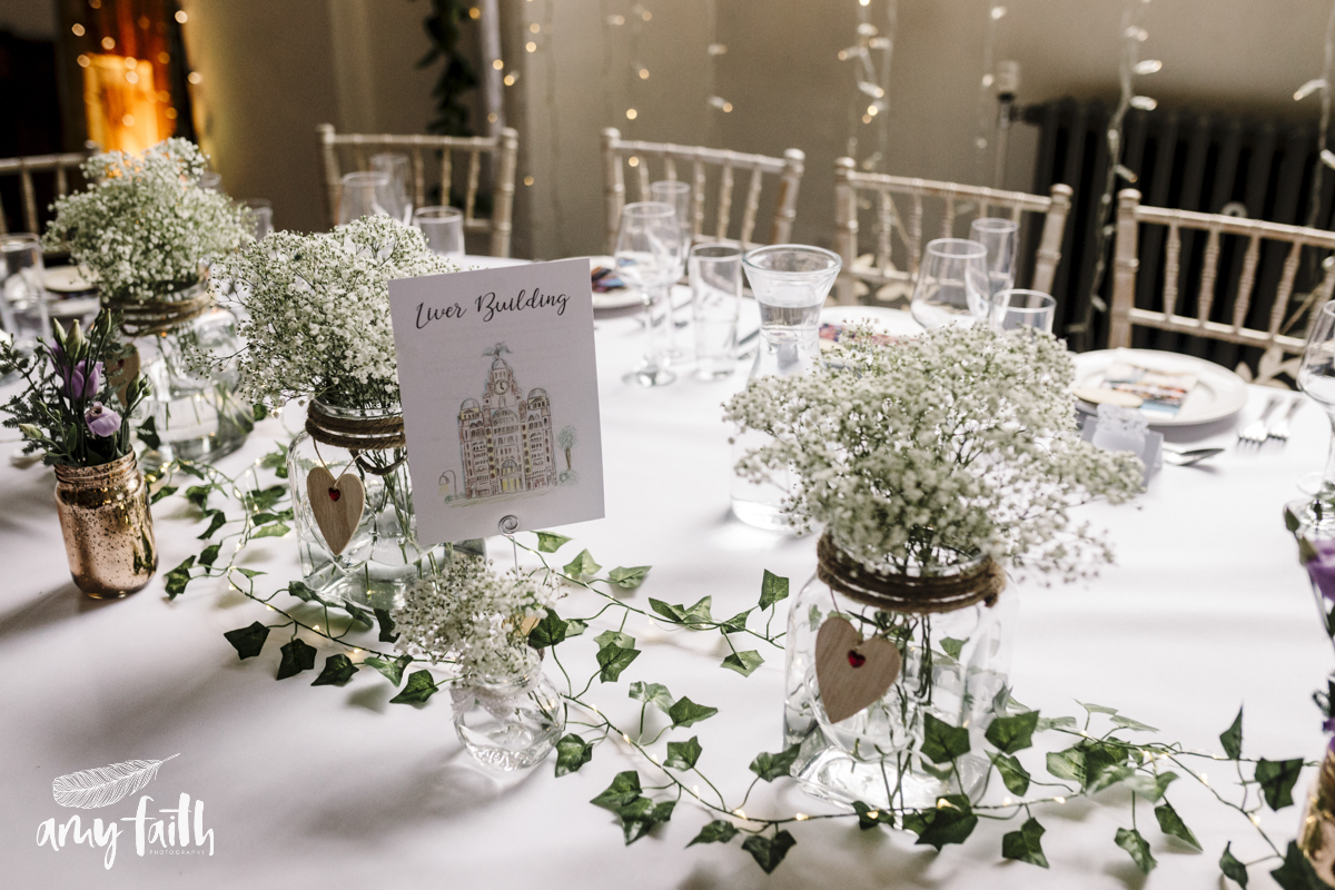 A table dressed in white linen with ivy trails.