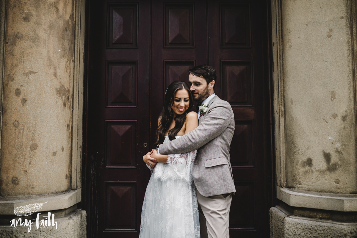 A bride and groom hugging in a doorway.