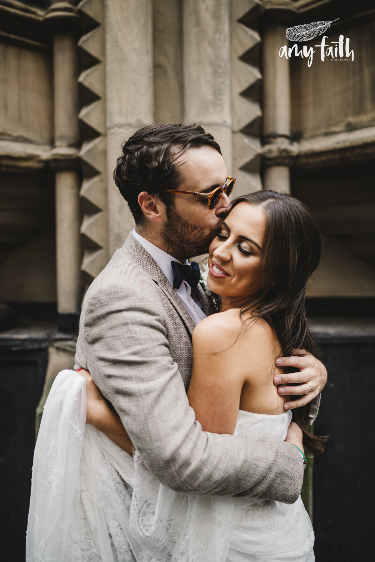 A groom in sunglasses kissing his bride.