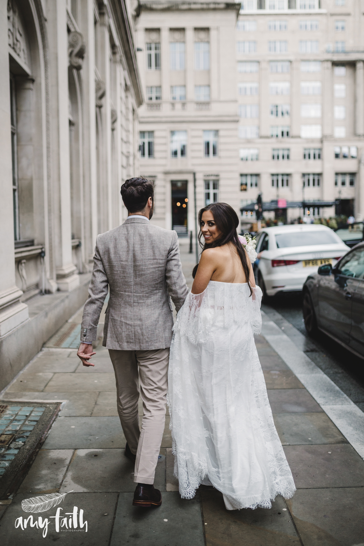 A bride and groom walking down a city street.